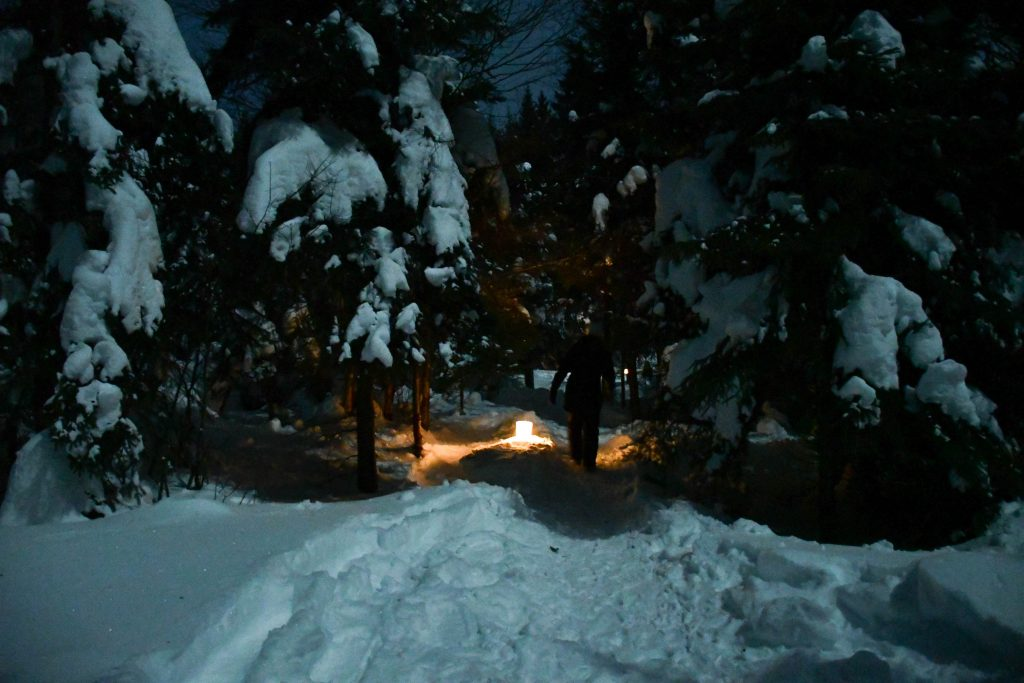Serenity among the heavy snow, moonlit night, and candlelit trails