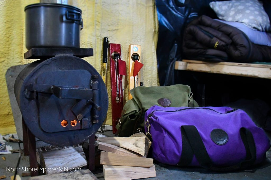 wood stove inside of ice fishing house with Duluth Packs